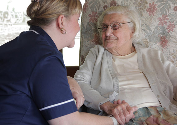 A nurse in a short sleeves blue top kneeling down talking to a lady in a chair who is holding her hand