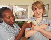 Two care nurses in light grey uniforms smiling holding two yellow chicks