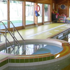 An indoor swimming pool with green and white tiles